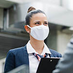 Attractive flight attendant talking to unrecognizable businessman on airport, wearing face masks.